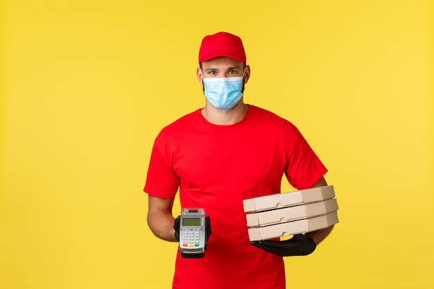 Dostawa jedzenia, śledzenie zamówień, koncepcja covid-19 i samodzielna kwarantanna. kurier w czerwonej jednolitej czapce i koszulce, masce medycznej, dający klientowi terminal pos i zamówienie na pizzę.