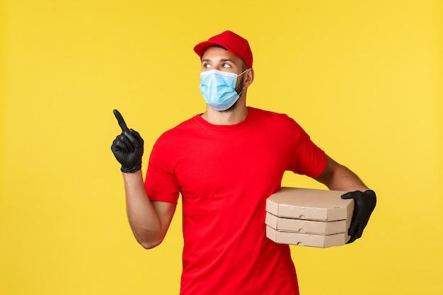 Dostawa jedzenia, śledzenie zamówień, koncepcja covid-19 i samodzielna kwarantanna. młody kurier przeszukuje dom, aby dostarczyć pizzę klientowi, spójrz w lewo, załóż czerwony mundur i osobiste wyposażenie ochronne