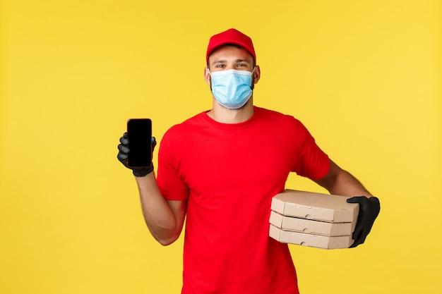 Dostawa jedzenia, śledzenie zamówień, koncepcja covid-19 i samodzielna kwarantanna. przyjazny uśmiechnięty kurier w czerwonym mundurze, masce medycznej i rękawiczkach, pokazujący aplikację na ekranie smartfona, przyniósł pizzę