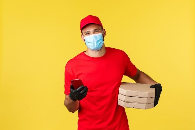 Dostawa jedzenia, śledzenie zamówień, koncepcja covid-19 i samodzielna kwarantanna. przyjazny uśmiechnięty kurier w czerwonym mundurze, pracownik za pomocą smartfona dzwoni do klienta przynoszącego zamówienia na pizzę, korzystając z aplikacji na telefonie