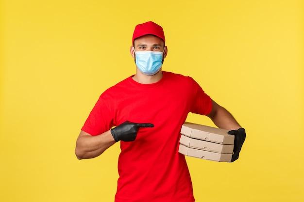 Dostawa jedzenia, śledzenie zamówień, koncepcja covid-19 i samodzielna kwarantanna. uśmiechnięty kurier wskazujący na pyszną pizzę, przynieś zamówienie do domu klienta, załóż rękawiczki ochronne i maskę medyczną