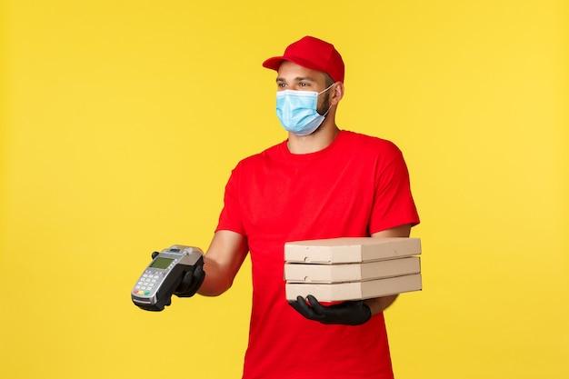 Dostawa jedzenia, śledzenie zamówień, koncepcja covid-19 i samodzielna kwarantanna. uśmiechnięty sympatyczny kurier w masce medycznej i czerwonym mundurze, rozdający klientom terminal płatniczy i pizzę, płacący zbliżeniowo za zamówienie