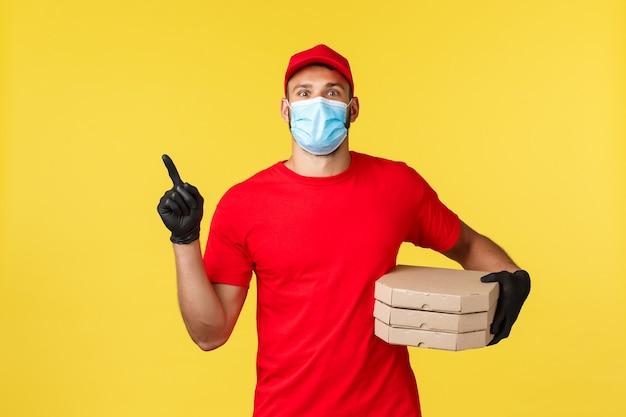 Dostawa jedzenia, śledzenie zamówień, koncepcja covid-19 i samodzielna kwarantanna. zadowolony przystojny kurier w czerwonym mundurze, masce medycznej i rękawiczkach, wskazujący w lewo, trzymający pizzę dla klienta