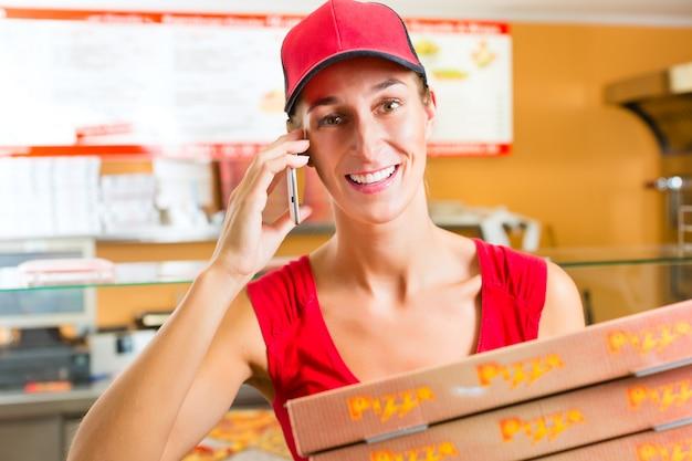 Dostawa, kobieta trzyma pudełka do pizzy