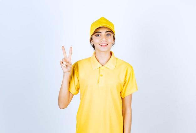 Dostawa kobieta w żółtym mundurze stoi i pokazuje znak zwycięstwa.