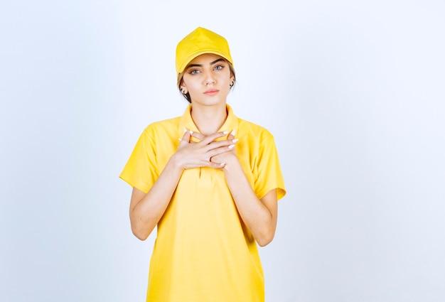 Dostawa kobieta w żółtym mundurze stojąc i patrząc na kamery poważnie.