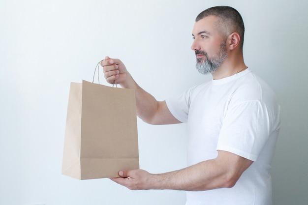 Dostawa kurierska i fast food. szczęśliwy brodaty mężczyzna z dużą rozporządzalną papierową torbą na białym tle