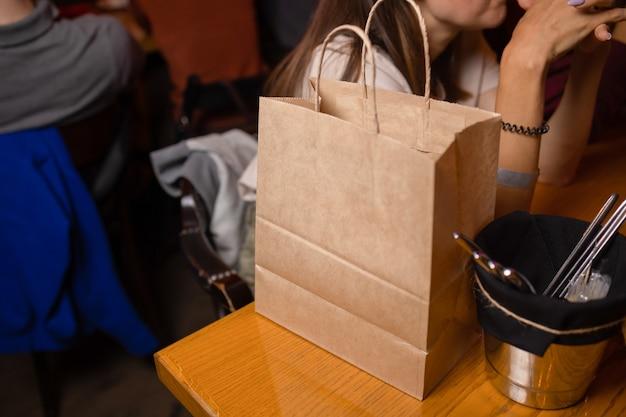 Dostawa kurierska usługi gastronomiczne w domu. kobieta kurier dostarczyła na zamówienie bezimienną torbę z jedzeniem.