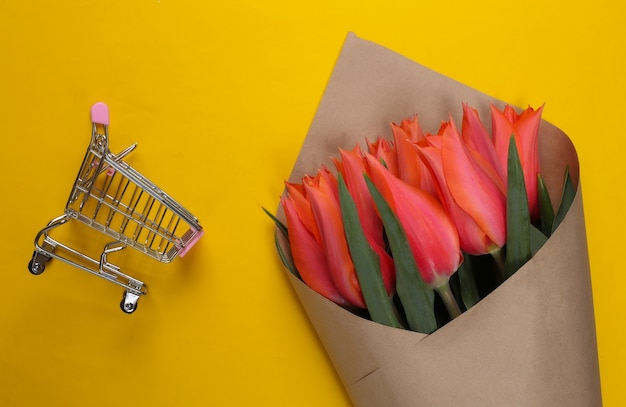 Dostawa kwiatów. bukiet tulipanów z wózkiem supermarketowym na żółto