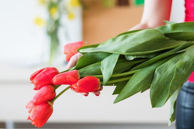 Dostawa kwiatów. kwiaciarnia trzyma bukiet czerwonych tulipanów. wiosenna świąteczna wiązka