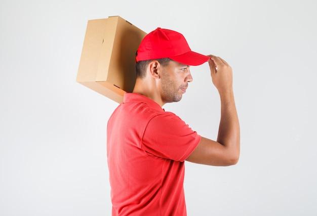 Dostawa mężczyzna trzyma karton na ramieniu w czerwonym mundurze i wygląda pozytywnie