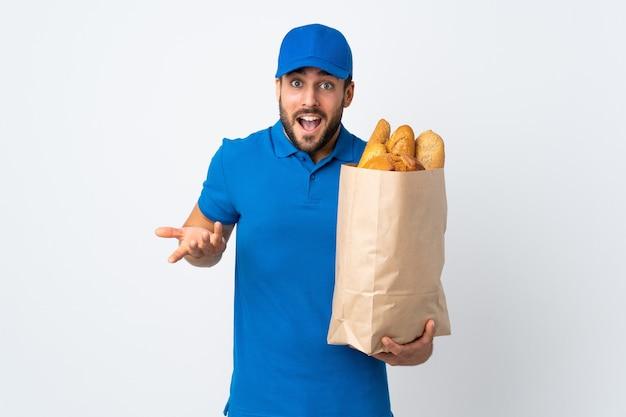 Dostawa mężczyzna trzyma torbę pełną pieczywa na białym tle na białej ścianie z zszokowanym wyrazem twarzy