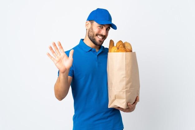Dostawa mężczyzna trzyma torbę pełną pieczywa na białym tle salutowanie ręką z happy wypowiedzi