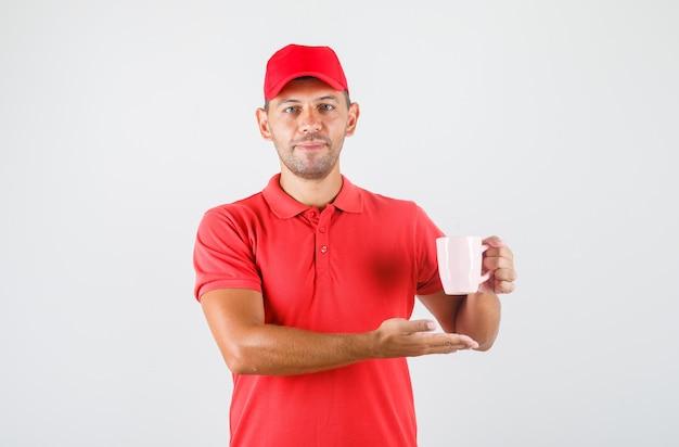 Dostawa mężczyzna w czerwonym mundurze trzymając kubek napoju i uśmiechnięty