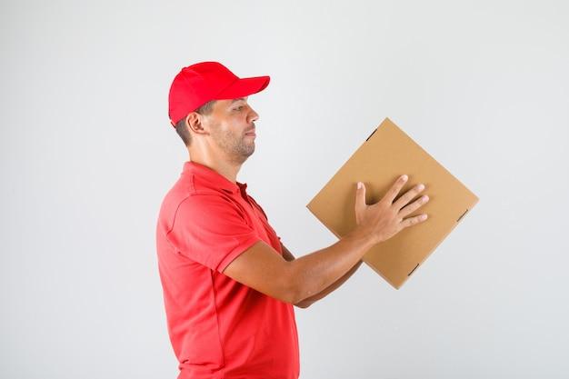 Dostawa mężczyzna w czerwonym mundurze, trzymając pudełko po pizzy.