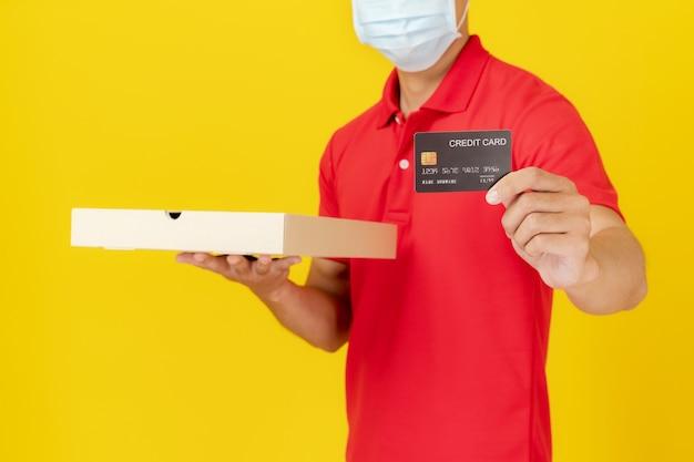 Dostawa mężczyzna w mundurze czerwonej koszulki polo z kartą kredytową