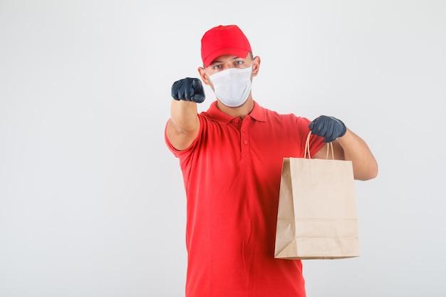 Dostawa mężczyzna wskazując palcem na aparat z papierową torbą w czerwonym mundurze, maska medyczna, rękawiczki