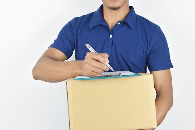 Dostawa młoda dostawa trzyma pudełko i pisze coś w schowku.