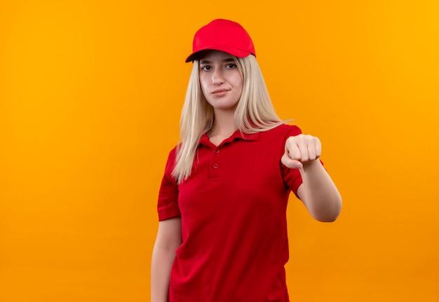 Dostawa młoda kobieta ma na sobie czerwoną koszulkę i czapkę wyciągając pięść na odizolowanych pomarańczowej ścianie