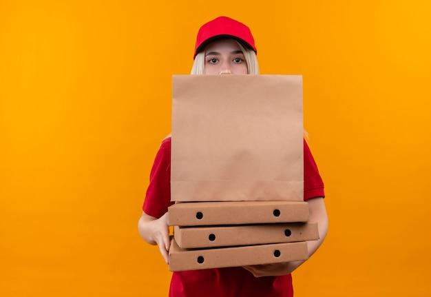 Dostawa młoda kobieta ubrana w czerwoną koszulkę i czapkę, trzymając pudełko po pizzy i papierową kieszeń na odizolowanych pomarańczowej ścianie