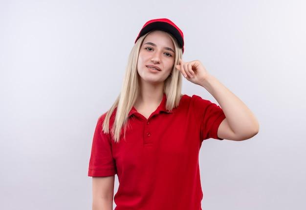 Dostawa młoda kobieta ubrana w czerwoną koszulkę i czapkę w ortezie dentystycznej położyła palec na głowie na odosobnionej białej ścianie
