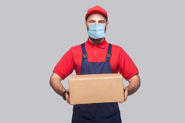 Dostawa na kwarantannie. portret młodego mężczyzny z chirurgiczną maską medyczną w niebieskim mundurze i czerwonej koszulce, stojąc i trzymając karton na szarym tle. wewnątrz, studio strzał, na białym tle,