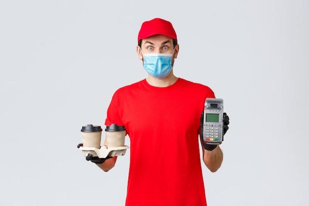 Dostawa na wynos, jedzenie i artykuły spożywcze, koncepcja zamówień zbliżeniowych covid-19. podekscytowany i zaskoczony klient lub pracownik w czerwonym mundurze, masce na twarz i rękawiczkach, wręczający klientowi terminal płatniczy kawą
