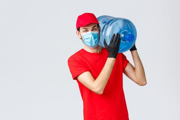 Dostawa na wynos, jedzenie i artykuły spożywcze, koncepcja zamówień zbliżeniowych covid-19. przyjazny kurier w czerwonym mundurze, czapce, masce i rękawiczkach, trzymający na ramieniu zamówienie na wodę butelkowaną