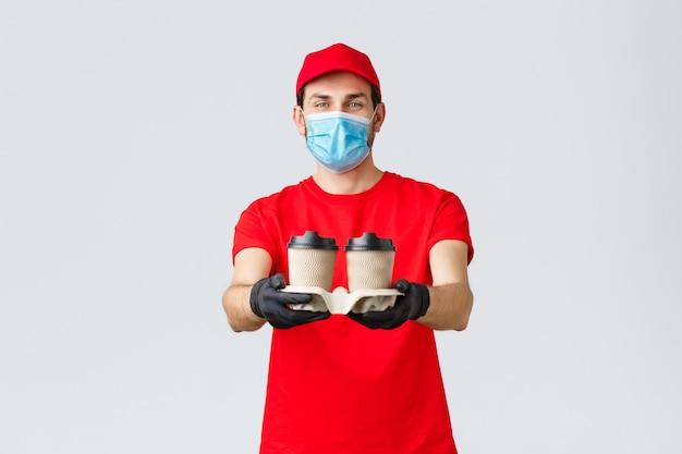 Dostawa na wynos, jedzenie i artykuły spożywcze, koncepcja zamówień zbliżeniowych covid-19. przyjazny młody kurier w czerwonym mundurze, masce na twarz i rękawiczkach, wydaje zamówienia, dostarcza napój do domu klienta.