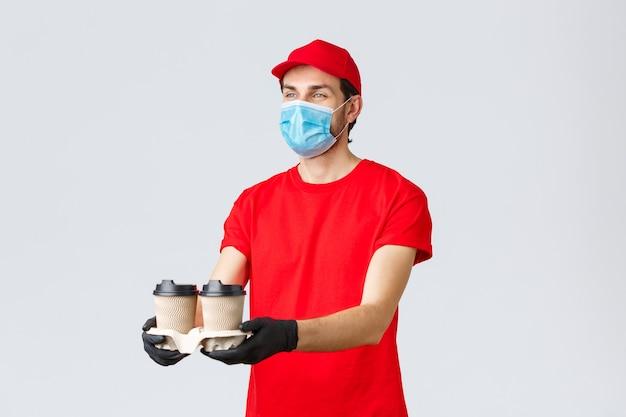 Dostawa na wynos, jedzenie i artykuły spożywcze, koncepcja zamówień zbliżeniowych covid-19. przyjemny kurier w czerwonym mundurze, masce na twarz i rękawiczkach, rozdając klientowi kawę, stoi na szarym tle