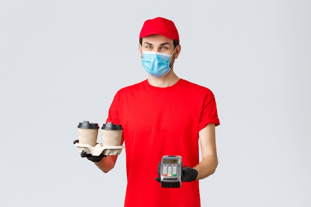 Dostawa na wynos, jedzenie i artykuły spożywcze, koncepcja zamówień zbliżeniowych covid-19. przyjemny kurier w czerwonym mundurze, rękawiczkach i masce na twarz, trzymający kawę dla klienta i terminala pos, szare tło