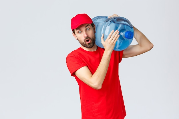 Dostawa na wynos, jedzenie i artykuły spożywcze, koncepcja zamówień zbliżeniowych covid-19. zaskoczony kurier w czerwonej czapce mundurowej i koszulce, z wrażeniem otwartych ust, trzymający na ramieniu wodę butelkowaną