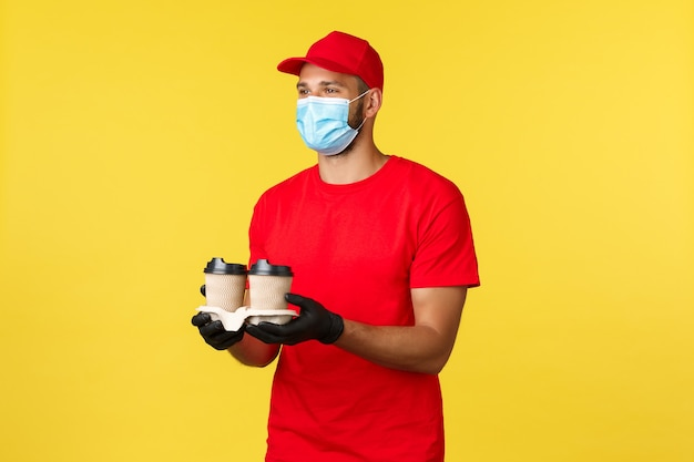 Dostawa na wynos, jedzenie i napoje, kwarantanna covid-19 i koncepcja zapobiegania wirusom. miły uśmiechnięty kurier przynosi porządek, przejeżdża przez pracownika wręczającego kawę klientowi, nosi maskę medyczną