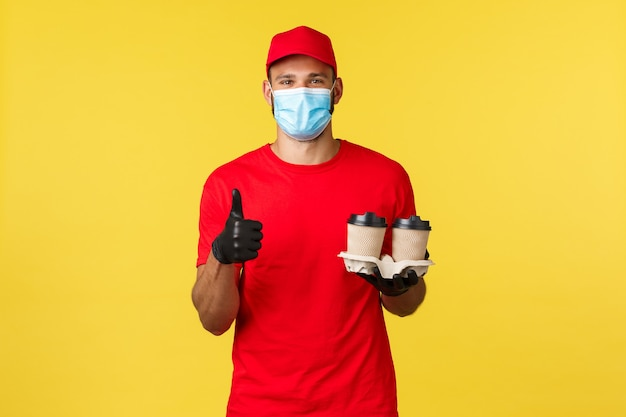 Dostawa na wynos, jedzenie i napoje, kwarantanna covid-19 i koncepcja zapobiegania wirusom. zadowolony kurier, pracownik w kawiarni przejeżdża, pokazuje kciuk w górę, podaje kawę w papierowych kubkach