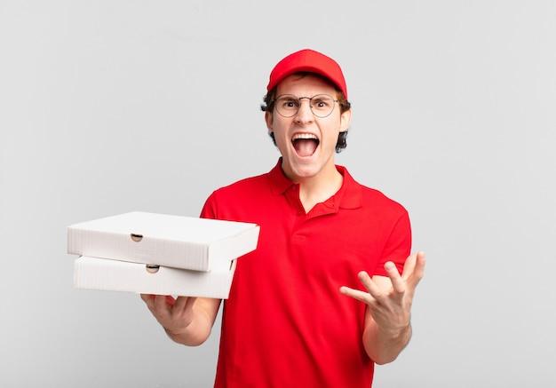 Dostawa pizzy chłopiec wyglądający na złego, zirytowanego i sfrustrowanego krzyczącego wtf lub co jest z tobą nie tak