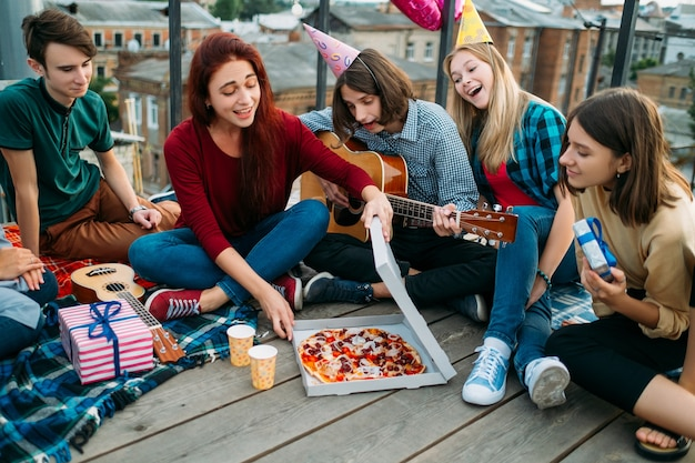 Dostawa pizzy na dach. niekonwencjonalne jedzenie urodzinowe. preferencje żywieniowe młodzieży. smaczne i pyszne jedzenie. szczęśliwe głodne nastolatki