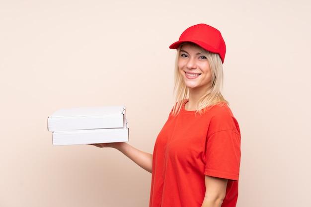 Dostawa pizzy rosjanka trzyma pizzę na izolowanej ścianie, uśmiechając się bardzo