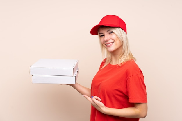 Dostawa pizzy rosyjska kobieta trzyma pizzę nad odosobnioną ścianą i wskazuje je