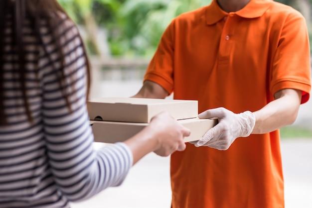 Dostawa pizzy w rękawicach ochronnych