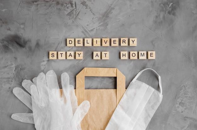 Dostawa produktów, żywności do domu. torba papierowa z maską ochronną i rękawiczkami na ciemnym betonowym tle. zostań w domu. poziomy, widok z góry, miejsce na kopię.
