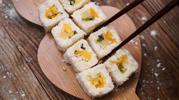 Dostawa sushi. słodkie bułeczki z ryżu, ananasa, kiwi i mango. rolki na drewnianym stole. drewniane patyczki do sushi.