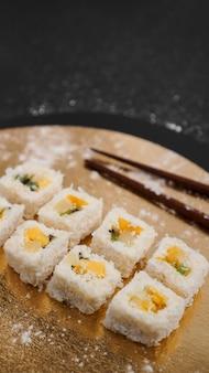 Dostawa sushi. słodkie bułeczki z ryżu, ananasa, kiwi i mango. rolki na złotym i czarnym tle. drewniane patyczki do sushi.