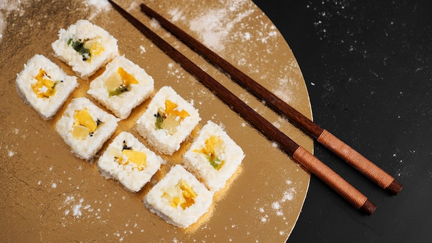 Dostawa sushi. słodkie bułeczki z ryżu, ananasa, kiwi i mango. toczy się na złotym i czarnym stole. drewniane patyczki do sushi.