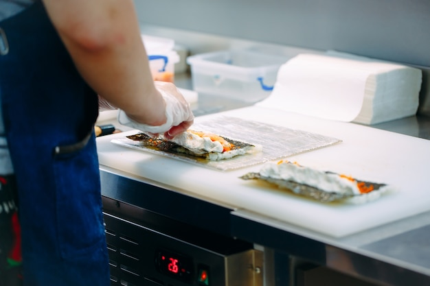 Dostawa sushi. szefowie kuchni w maskach i rękawiczkach przygotowują sushi w kuchni restauracji.