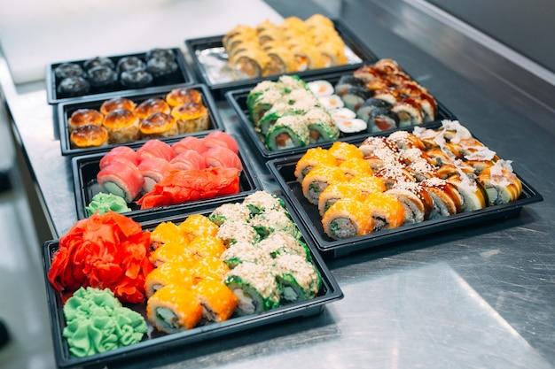 Dostawa sushi. wiele odmian sushi w plastikowym pudełku jest przygotowanych do dostawy.