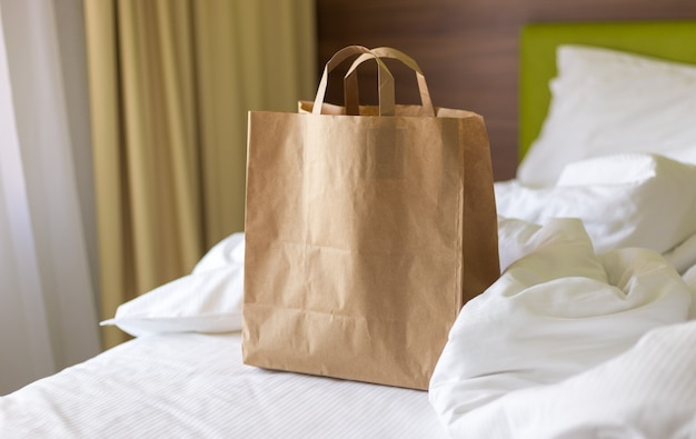 Dostawa torby rzemieślniczej żywności na łóżku w słoneczny dzień. dostawa w każdą pogodę przez całą dobę do klienta. ekologiczne opakowanie fast food z dużym zestawem śniadaniowym