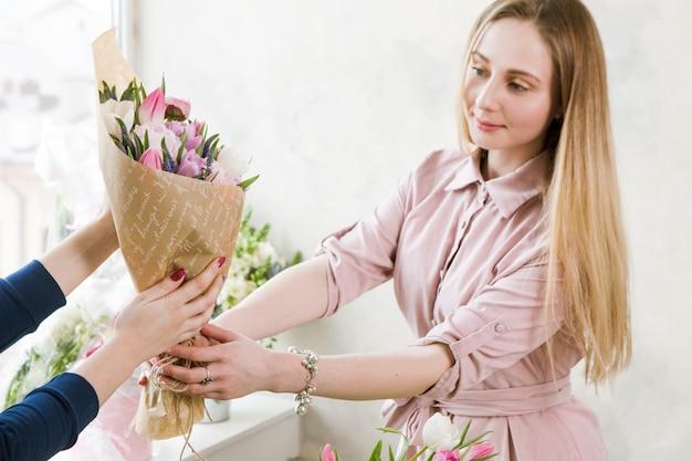 Dostawa warsztatu florystycznego. klient otrzymuje swoje zamówienie – bukiet różowego tulipana. kwiaciarnia ręczna przekazuje kwiaty kupującemu