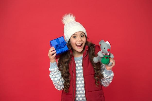Dostawa. zaintrygowany nieoczekiwaną przesyłką. pomysł na prezent świąteczny. ferie. szczęśliwy strój zimowy dziecko trzymać pudełko czerwone tło. prezenty świąteczne. koncepcja pamiątek z wakacji. prezent dla kobiety.