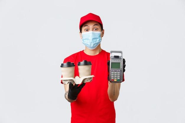 Dostawa zbliżeniowa, bezpieczny zakup i zakupy podczas koncepcji koronawirusa. azjatycki kurier lub pracownik fast food pokazujący terminal pos i kawę, płacący terminal klientowi, szare tło