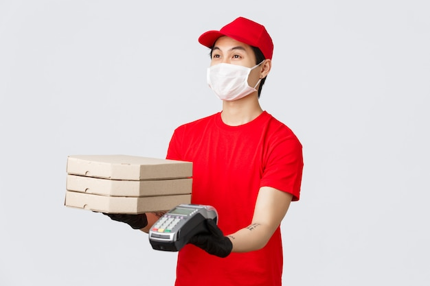 Dostawa zbliżeniowa, bezpieczny zakup i zakupy podczas koncepcji koronawirusa. przyjazny kurier w czerwonej czapce i koszulce w mundurze, dający klientowi zamówienie na pizzę i terminal płatniczy, szare tło